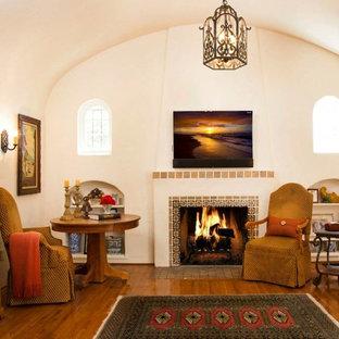 サンディエゴの大きい地中海スタイルのおしゃれな独立型リビング (フォーマル、ベージュの壁、無垢フローリング、標準型暖炉、タイルの暖炉まわり、壁掛け型テレビ) の写真