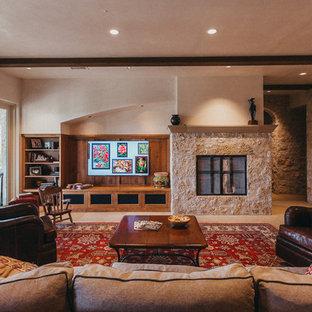 オースティンの中サイズのサンタフェスタイルのおしゃれな独立型リビング (フォーマル、マルチカラーの壁、ライムストーンの床、標準型暖炉、石材の暖炉まわり、壁掛け型テレビ、ベージュの床) の写真
