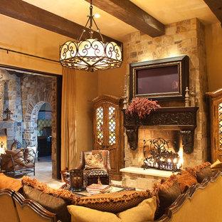 フェニックスの巨大なラスティックスタイルのおしゃれな独立型リビング (フォーマル、茶色い壁、トラバーチンの床、標準型暖炉、石材の暖炉まわり、壁掛け型テレビ) の写真