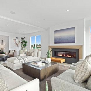 オレンジカウンティの大きいビーチスタイルのおしゃれなLDK (フォーマル、白い壁、ライムストーンの床、横長型暖炉、タイルの暖炉まわり、テレビなし、白い床) の写真
