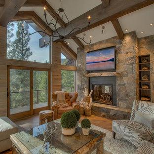 Inspiration pour un très grand salon chalet ouvert avec un sol en bois brun, une cheminée standard, un manteau de cheminée en pierre, un téléviseur fixé au mur et un mur blanc.