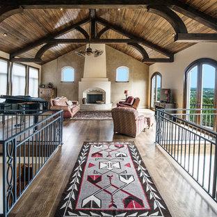 Idéer för ett amerikanskt loftrum, med beige väggar, mörkt trägolv, en standard öppen spis, en spiselkrans i gips och en fristående TV
