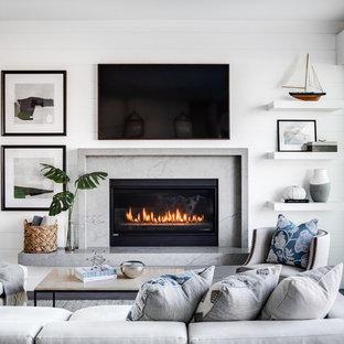 ロサンゼルスの中サイズのビーチスタイルのおしゃれなLDK (白い壁、標準型暖炉、壁掛け型テレビ、無垢フローリング、石材の暖炉まわり、茶色い床) の写真