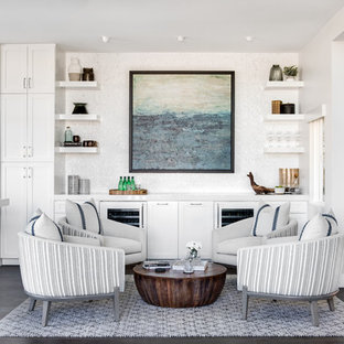 Inspiration for a mid-sized coastal open concept medium tone wood floor and brown floor living room remodel in Los Angeles with a bar, white walls, a standard fireplace and a stone fireplace