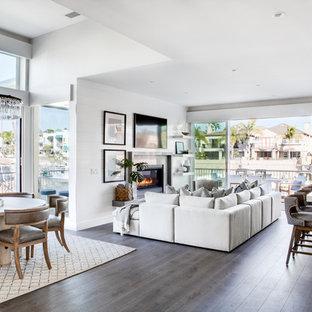 ロサンゼルスの大きいビーチスタイルのおしゃれなLDK (白い壁、無垢フローリング、標準型暖炉、石材の暖炉まわり、壁掛け型テレビ、茶色い床) の写真