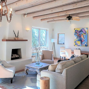 Example of a mid-sized southwest formal and open concept brick floor living room design in Albuquerque with white walls, a standard fireplace, a plaster fireplace and no tv