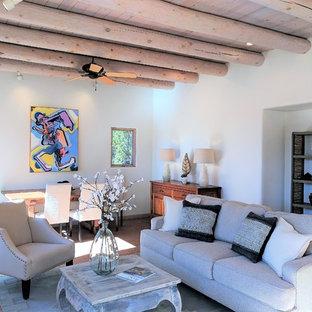 アルバカーキの中くらいのサンタフェスタイルのおしゃれなLDK (フォーマル、白い壁、レンガの床、標準型暖炉、漆喰の暖炉まわり、テレビなし) の写真