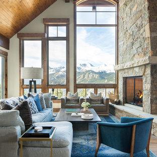 Idée de décoration pour un salon chalet avec un mur blanc, un sol en bois brun, une cheminée standard, un manteau de cheminée en pierre et un sol marron.