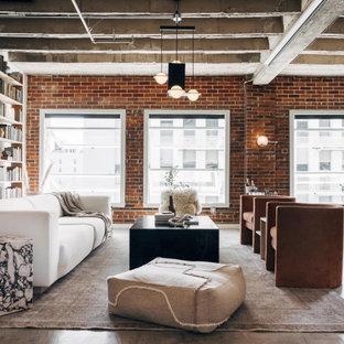 Cette image montre un très grand salon avec une bibliothèque ou un coin lecture urbain ouvert avec un mur rouge, béton au sol, aucune cheminée, un sol gris, un plafond en poutres apparentes et un mur en parement de brique.