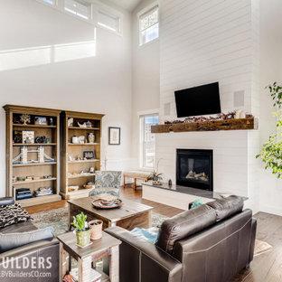 Foto di un soggiorno country aperto con pavimento in legno massello medio, camino classico, cornice del camino in perlinato, TV a parete, pavimento marrone e boiserie