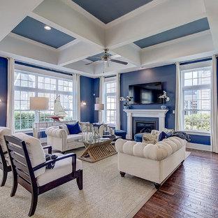 Aménagement d'un salon classique de taille moyenne et ouvert avec un mur bleu, un sol en bois brun, une cheminée standard, un manteau de cheminée en bois, un téléviseur fixé au mur, un sol marron, un plafond à caissons et boiseries.