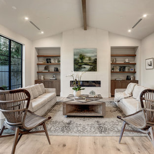 ヒューストンの大きいトランジショナルスタイルのおしゃれなLDK (白い壁、淡色無垢フローリング、標準型暖炉、石材の暖炉まわり、壁掛け型テレビ、白い床) の写真