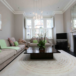 This is an example of a contemporary enclosed living room in London with grey walls, carpet, a standard fireplace, a plastered fireplace surround, a freestanding tv and beige floors.