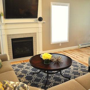 Esempio di un soggiorno classico di medie dimensioni e aperto con pareti grigie, parquet chiaro, camino classico, cornice del camino piastrellata e TV a parete