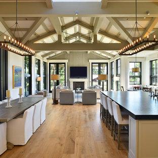 Inspiration pour un grand salon rustique ouvert avec une salle de réception, un mur gris, un sol en bois clair, une cheminée standard, un manteau de cheminée en béton, un téléviseur fixé au mur et un sol beige.