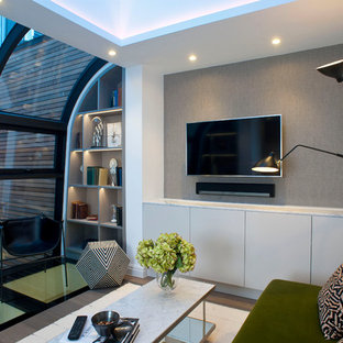 Photo of a contemporary living room in London with grey walls, medium hardwood flooring, a wall mounted tv and brown floors.