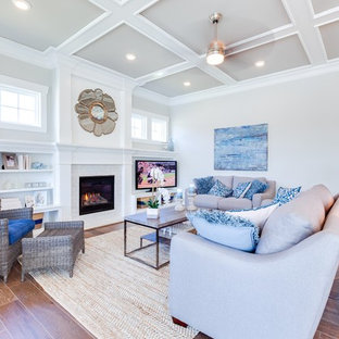 Example of a large coastal open concept medium tone wood floor living room design in Other with gray walls, a standard fireplace, a tile fireplace and a media wall