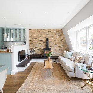 Lantlig inredning av ett allrum med öppen planlösning, med ett finrum, vita väggar, mellanmörkt trägolv, en öppen vedspis och en väggmonterad TV