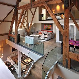 Ejemplo de salón tipo loft, actual, con suelo de madera en tonos medios y suelo beige