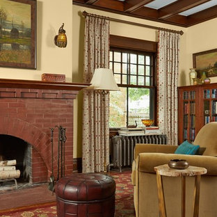 Example of an arts and crafts red floor living room design in Minneapolis with beige walls, a standard fireplace and a brick fireplace