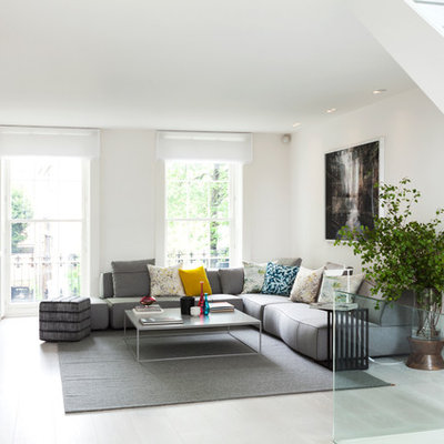Example of a mid-sized trendy formal and open concept light wood floor living room design in London with white walls, a standard fireplace, a stone fireplace and no tv