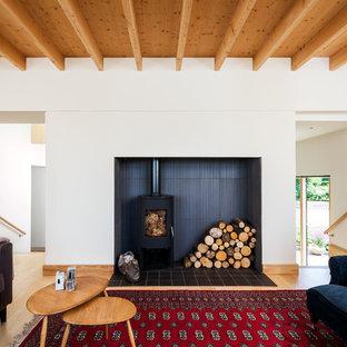 Foto di un soggiorno scandinavo aperto con pareti bianche, pavimento in legno massello medio e stufa a legna