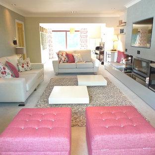 Esempio di un grande soggiorno minimalista con pareti beige, moquette, camino lineare Ribbon, cornice del camino in intonaco, parete attrezzata e pavimento beige