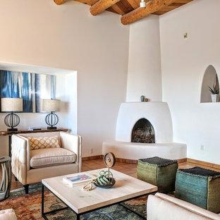 他の地域の中サイズのサンタフェスタイルのおしゃれなリビング (テラコッタタイルの床、コーナー設置型暖炉、漆喰の暖炉まわり、テレビなし、オレンジの床、フォーマル、ベージュの壁) の写真