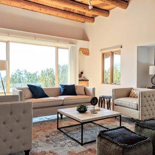 他の地域の中サイズのサンタフェスタイルのおしゃれなLDK (白い壁、テラコッタタイルの床、コーナー設置型暖炉、漆喰の暖炉まわり、テレビなし、オレンジの床) の写真