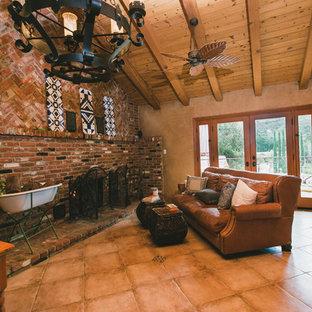 他の地域のエクレクティックスタイルのおしゃれなリビング (茶色い壁、テラコッタタイルの床、薪ストーブ、レンガの暖炉まわり、茶色い床) の写真