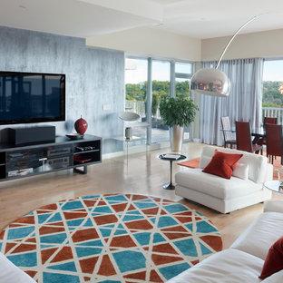 Inredning av ett modernt mellanstort allrum med öppen planlösning, med grå väggar, ljust trägolv, en väggmonterad TV och beiget golv