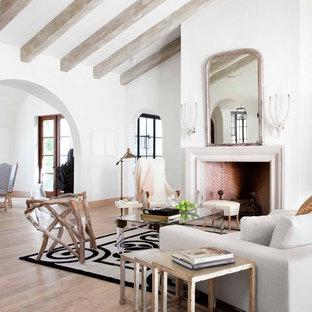 Immagine di un soggiorno mediterraneo con pareti bianche, pavimento in legno massello medio e camino classico
