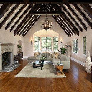 Cette image montre un grand salon traditionnel fermé avec un mur beige, une salle de réception, un sol en bois brun, une cheminée standard et un manteau de cheminée en plâtre.