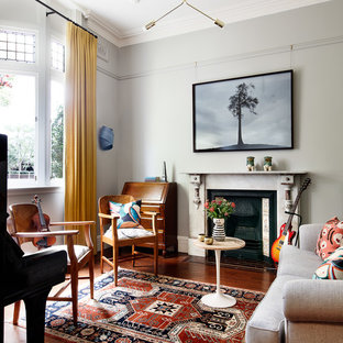 Photo of an eclectic living room in Sydney with grey walls, medium hardwood floors, a standard fireplace and brown floor.