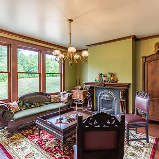 Design ideas for a large victorian living room in Seattle with green walls, medium hardwood flooring, a standard fireplace and brown floors.