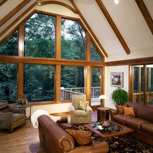 Foto di un grande soggiorno tropicale stile loft con pareti beige e pavimento in legno massello medio