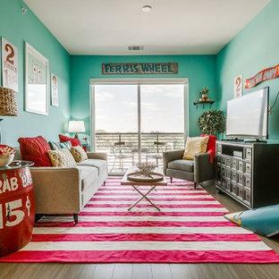 Immagine di un soggiorno boho chic con pareti verdi, pavimento in legno massello medio, TV autoportante e pavimento marrone