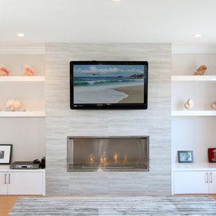 Imagen de salón cerrado, moderno, de tamaño medio, con paredes beige, suelo de madera clara, chimeneas suspendidas, marco de chimenea de baldosas y/o azulejos y televisor colgado en la pared