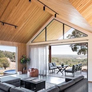 Country Wohnzimmer mit brauner Wandfarbe, Betonboden, grauem Boden, gewölbter Decke, Holzdecke und Holzwänden in Perth