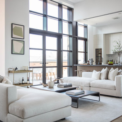 Trendy open concept light wood floor living room photo in New York with white walls and a bar