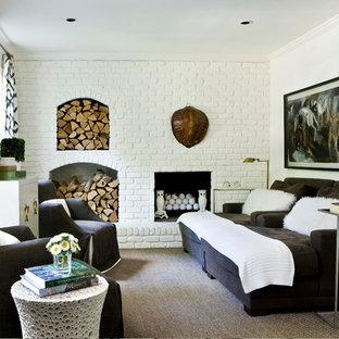 Esempio di un soggiorno design chiuso con pareti bianche, camino classico e cornice del camino in mattoni