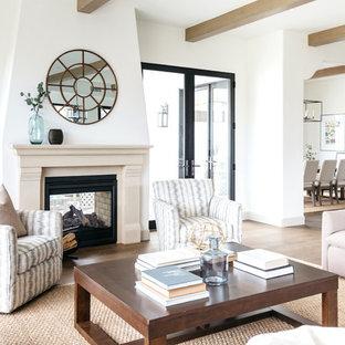 ロサンゼルスの地中海スタイルのおしゃれなLDK (フォーマル、白い壁、淡色無垢フローリング、両方向型暖炉、テレビなし) の写真