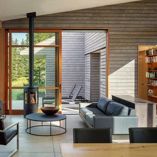 Modelo de salón abierto, actual, de tamaño medio, sin televisor, con paredes grises, suelo de cemento, estufa de leña, marco de chimenea de hormigón y suelo gris