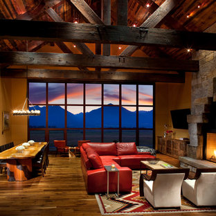 Living room - rustic open concept dark wood floor living room idea in Other with orange walls, a standard fireplace, a stone fireplace and a wall-mounted tv