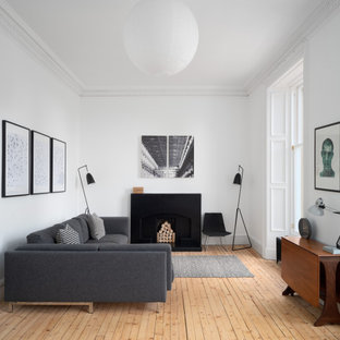 This is an example of a medium sized scandinavian formal enclosed living room in Edinburgh with white walls, medium hardwood flooring, no tv and beige floors.