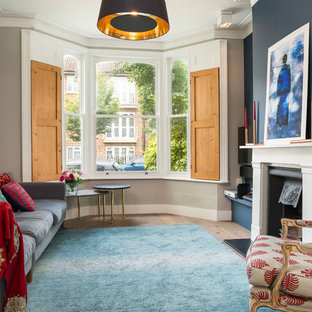 Design ideas for a medium sized contemporary formal living room in London with blue walls, a standard fireplace and a wall mounted tv.