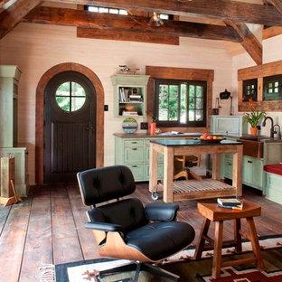 Cette image montre un petit salon chalet ouvert avec un mur beige et un sol en bois brun.