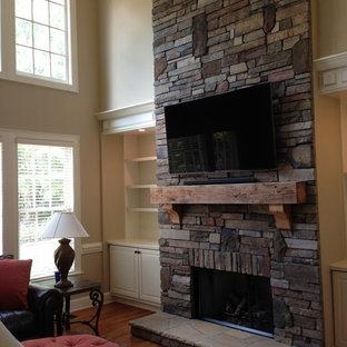 Imagen de salón abierto, tradicional, de tamaño medio, con chimenea tradicional, marco de chimenea de piedra, televisor colgado en la pared, paredes beige y suelo de madera oscura