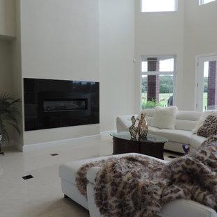 他の地域の巨大なトランジショナルスタイルのおしゃれなLDK (フォーマル、ベージュの壁、磁器タイルの床、吊り下げ式暖炉、石材の暖炉まわり、埋込式メディアウォール、白い床) の写真