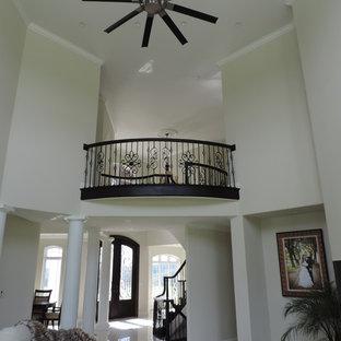 他の地域の巨大なトランジショナルスタイルのおしゃれなLDK (フォーマル、ベージュの壁、磁器タイルの床、吊り下げ式暖炉、埋込式メディアウォール、白い床) の写真